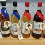 four bottles of mead with their mead fest winner's medals