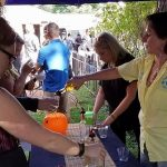 a woman in a yellow shirt pouring mead for a patron at mead fest