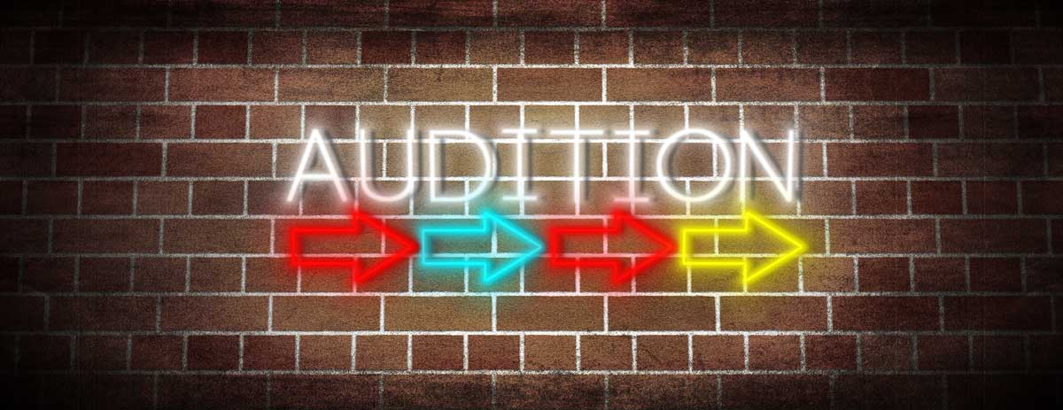 neon sign reads audition with colored arrows